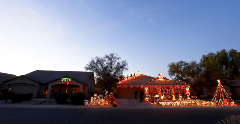 "Unable to compete with her neighbor, Eric Cyr, Kristina Green opted to decorate her home, left, with a 450-light ""Ditto"" sign and an arrow pointing to Cyr's 20,000-light Christmas display, as shown Tuesday, Dec. 11, 2012 in Maricopa, Ariz. (AP Photo/Ross D. Franklin)"