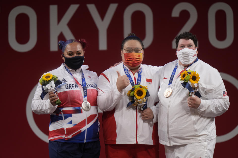 Gold medalist Li Wenwen of China, center, poses with silver medalist Emily Jade Campbell of Britain, left, and bronze medalist Sarah Elizabeth Robles of the United States, in the medals ceremony for the women's +87kg weightlifting at the 2020 Summer Olympics, Monday, Aug. 2, 2021, in Tokyo, Japan. (AP Photo/Luca Bruno)