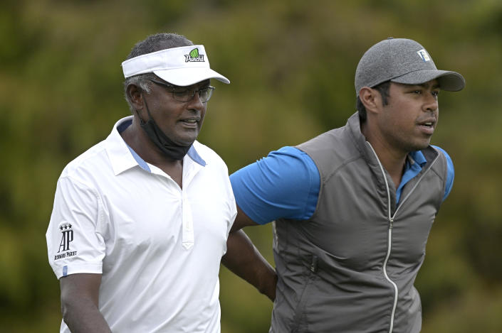 Vijay Singh, left, and his son Qass walk on the 18th fairway after hitting their tee shots during the first round of the PNC Championship golf tournament, Saturday, Dec. 19, 2020, in Orlando, Fla. (AP Photo/Phelan M. Ebenhack)