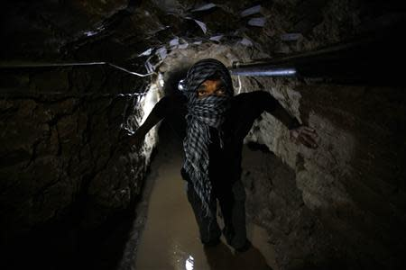 A Palestinian works inside a smuggling tunnel flooded by Egyptian forces, beneath the Egyptian-Gaza border in Rafah, in the southern Gaza Strip in this February 19, 2013 file photo. REUTERS/Ibraheem Abu Mustafa/Files