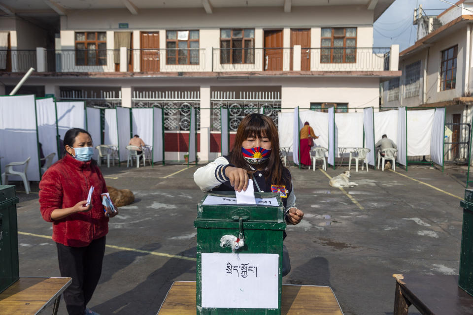 An exile Tibetan wearing a mask printed in the colours of a Tibetan flag casts her vote in Dharmsala, India, Sunday, Jan. 3, 2021. Exile Tibetans Sunday voted in the first round to elect a new political leader and members of the Tibetan parliament in exile. (AP Photo/Ashwini Bhatia)