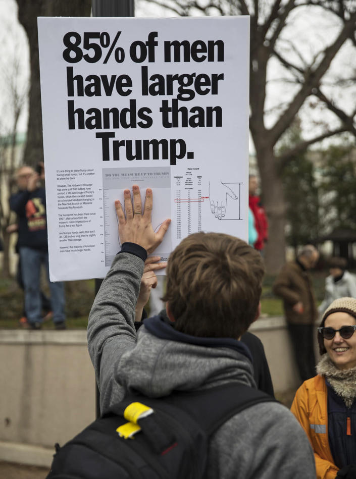 <p>A demonstrator attending the Women's March in Washington holds up his hand to a poster critical of President Donald Trump, Jan. 21, 2017. (Photo: Robert Nickelsberg/Getty Images) </p>