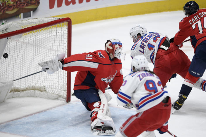 New York Rangers left wing Alexis Lafrenière (13) scores a goal past Washington Capitals goaltender Vitek Vanecek (41) during the second period of an NHL hockey game, Saturday, Feb. 20, 2021, in Washington. Also seen are Capitals defenseman John Carlson (74) and Rangers center Mika Zibanejad (93). (AP Photo/Nick Wass)