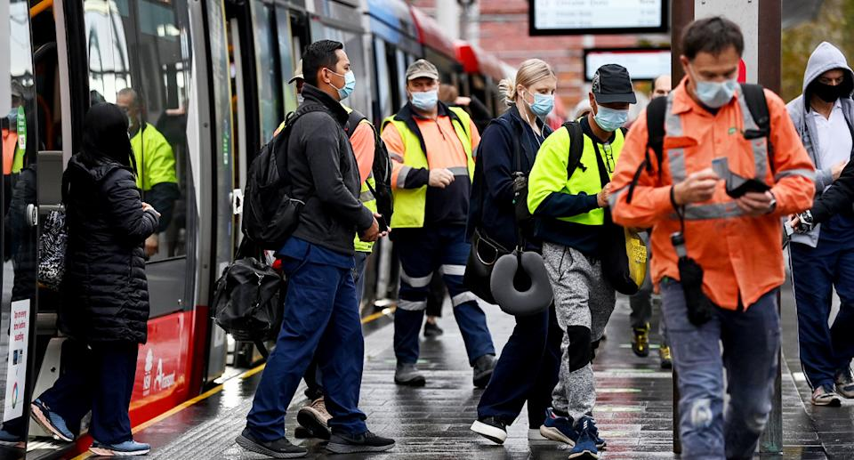 A group of masked workers exit a tram in Sydney's CBD.
