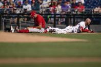 Philadelphia Phillies first baseman Rhys Hoskins, left, and Washington Nationals' Yadiel Hernandez react after colliding on a throwing error by starting pitcher Aaron Nola in the second inning of a baseball game, Thursday, Aug. 5, 2021, in Washington. (AP Photo/Patrick Semansky)