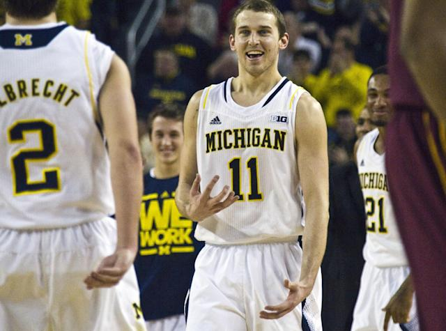 Michigan guard Nik Stauskas (11) gestures at guard Spike Albrecht (2) during the second half of an NCAA college basketball game against Minnesota at Crisler Center in Ann Arbor, Mich., Saturday, March 1, 2014. Michigan won 66-56. (AP Photo/Tony Ding)