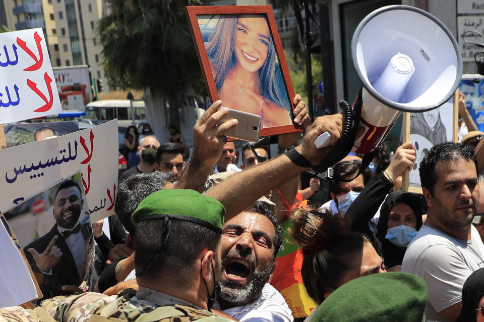 A man who lost his son during last year's massive blast at Beirut's seaport, shouts slogans as he pushed back by a Lebanese army soldier after he tries with others to reach the tightly-secured residence of parliament speaker Nabih Berri, in Beirut, Lebanon, Friday, July 9, 2021. The protest came after last week's decision by the judge to pursue senior politicians and former and current security chiefs in the case, and requested permission for their prosecution. (AP Photo/Hussein Malla)