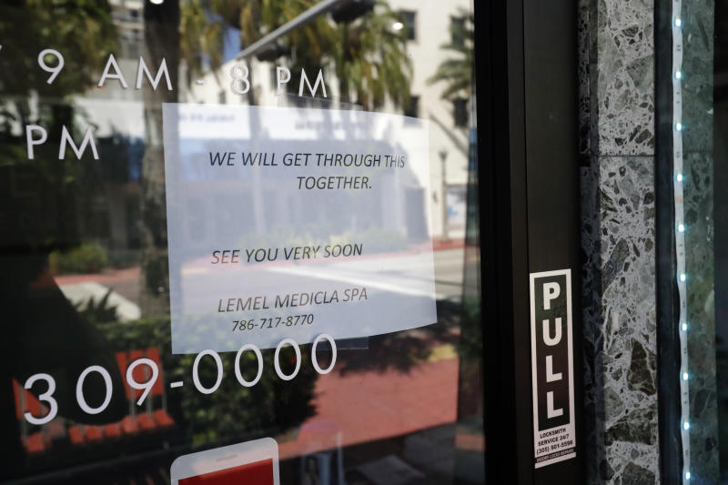 "A sign indicates a closed business Saturday, March 21, 2020, in downtown Surfside, Fla. Miami-Dade County's mayor on Thursday ordered all beaches, parks and ""non-essential"" commercial and retail businesses closed because of the coronavirus pandemic. (AP Photo/Wilfredo Lee)"