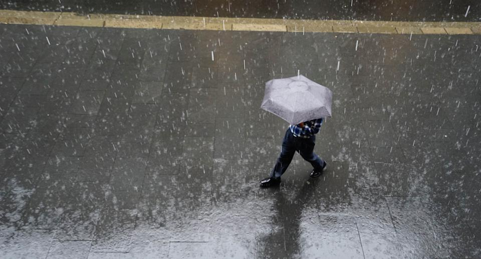 Stock image of a pedestrian making their way through extreme weather and rain in Sydney, Australia. Source: Getty Images