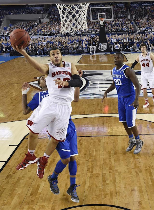 Wisconsin guard Traevon Jackson (12) drives to the basket past Kentucky's James Young, left, and Julius Randle (30) during the second half of an NCAA Final Four tournament college basketball semifinal game Saturday, April 5, 2014, in Arlington, Texas. Kentucky won 74-73. (AP Photo/Chris Steppig, pool)