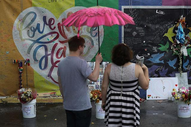 <p>Dalton Hoffine and Nicole Stark (L-R) visit the memorial to the victims of the mass shooting setup around the Pulse gay nightclub one day before the one year anniversary of the shooting on June 11, 2017 in Orlando, Florida. (Joe Raedle/Getty Images) </p>