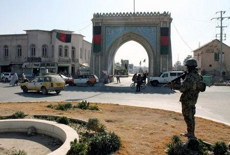 An Afghan National Army soldier stands guard near the Kandahar governor guest house building where a bomb blast killed mainly government officials or diplomats from the United Arab Emirates, in Kandahar