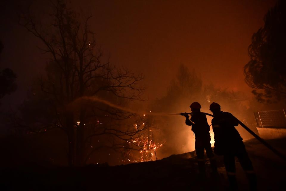 Firefighters try to extinguish a wildfire in Afidnes area, northern Athens, Greece, Thursday, Aug. 5, 2021. Wildfires rekindled outside Athens and forced more evacuations around southern Greece Thursday as weather conditions worsened and firefighters in a round-the-clock battle stopped the flames just outside the birthplace of the ancient Olympics. (AP Photo/Michael Varaklas)