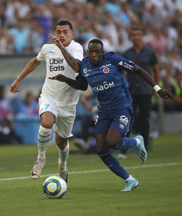 Reims' Hassane Kamara, right, is challenged by Marseille's Nemanja Radonjic during the French League One soccer match between Marseille and Reims at the Velodrome Stadium in Marseille, France, Saturday, Aug. 10, 2019. (AP Photo/Daniel Cole)