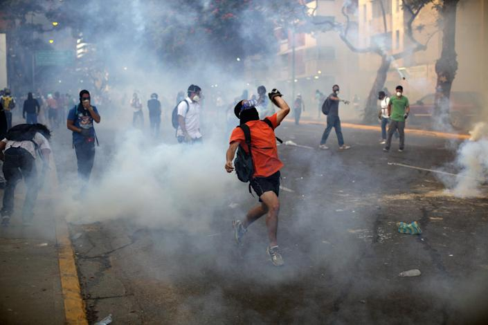 Demonstrators throw objects amid tear gas launched by the Bolivarian National Police (BNP) in the Altamira neighborhood of Caracas, Venezuela, Wednesday, Feb. 19, 2014. Venezuelan security forces backed by water tanks and tear gas dispersed groups of anti-government demonstrators who tried to block Caracas' main highway Wednesday evening. (AP Photo/Rodrigo Abd)