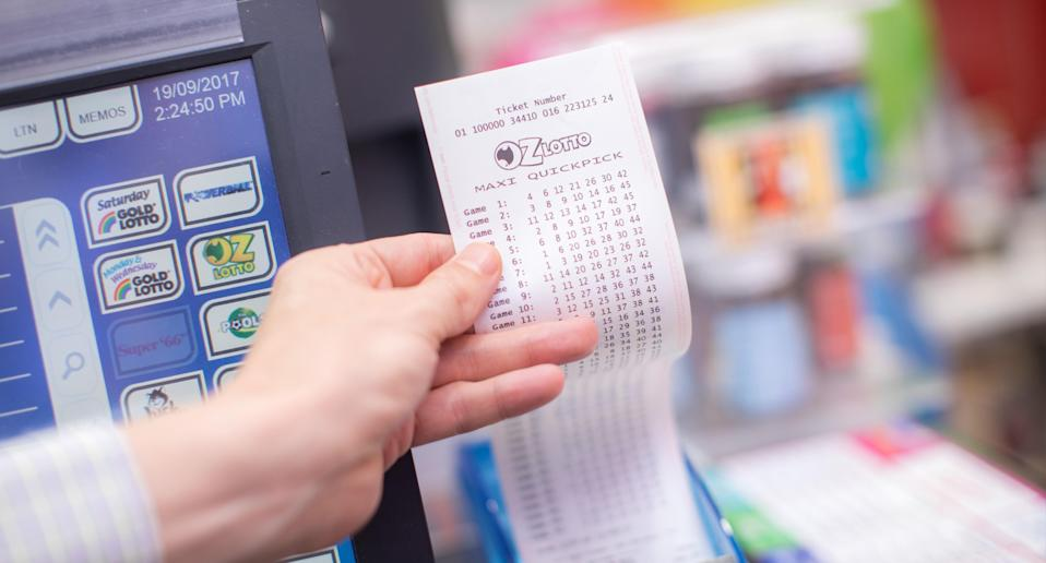 A man holds an Oz Lotto ticket in a newsagent.