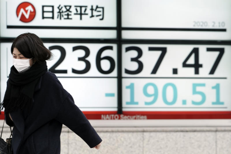 A woman walks past an electronic stock board showing Japan's Nikkei 225 index at a securities firm in Tokyo Monday, Feb. 10, 2020. Asian stock markets slid Monday after China reported an uptick in new cases of its virus outbreak and analysts warned optimism the disease is under control might be premature. (AP Photo/Eugene Hoshiko)