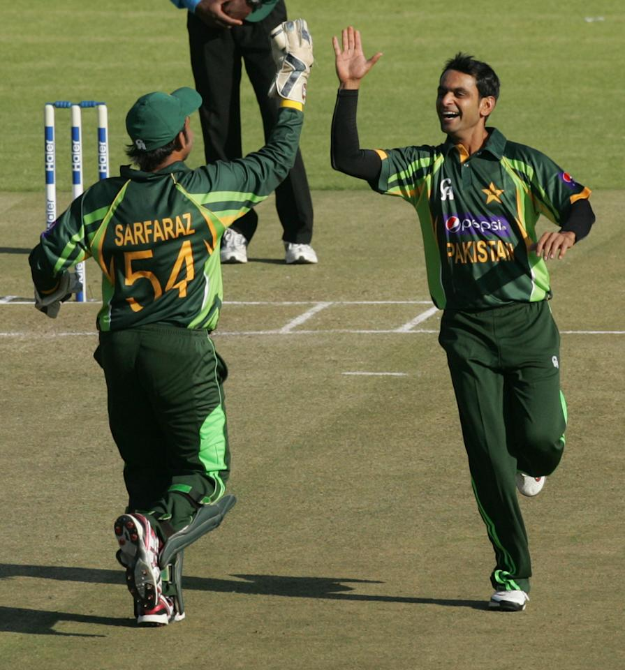 Pakistan's captain Muhammad Hafeez (R) celebrates a wicket with wicket keeper Safraz Ahmed during the second and final Twenty20 international between Zimbabwe and Pakistan at the Harare Sports Club on August 24, 2013.   AFP PHOTO / JEKESAI NJIKIZANA        (Photo credit should read JEKESAI NJIKIZANA/AFP/Getty Images)