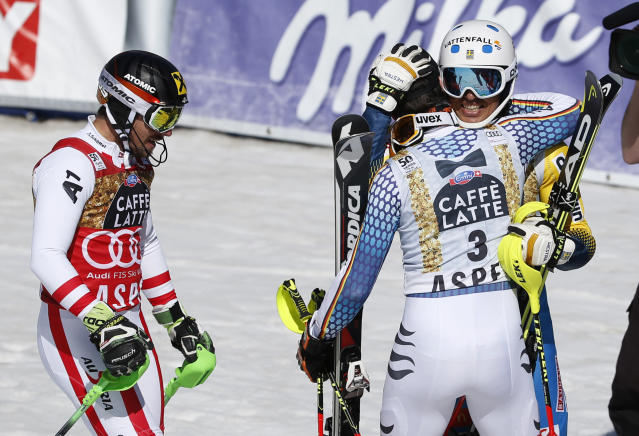 Sweden's Andre Myhrer, right, hugs Germany's Felix Neureuther as Austria's Marcel Hirscher, left, skis off after the second run of a men's World Cup slalom ski race Sunday, March 19, 2017, in Aspen, Colo. (AP Photo/Brennan Linsley)