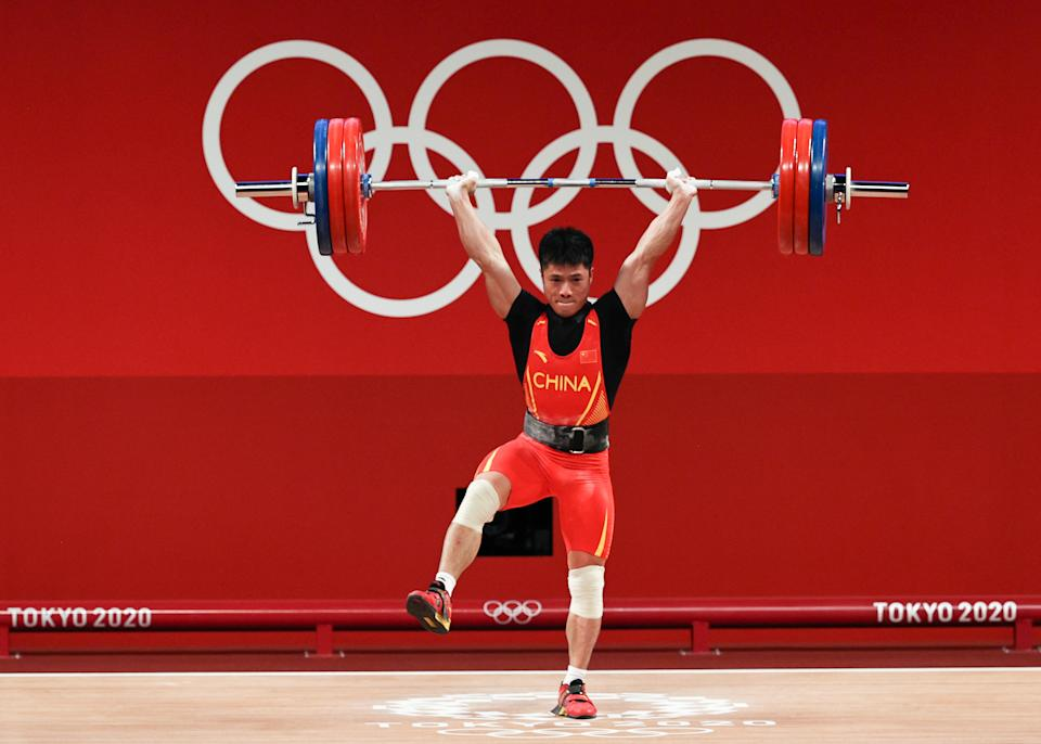 <p>TOKYO, JAPAN - JULY 25: Fabin Li of Team China competes during the Weightlifting - Men's 61kg Group A on day two of the Tokyo 2020 Olympic Games at Tokyo International Forum on July 25, 2021 in Tokyo, Japan. (Photo by Chris Graythen/Getty Images)</p>
