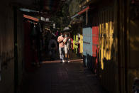 """Alexia Thorpe and her boyfriend, Bennett Olupo are lit by afternoon sunlight as they stroll past stalls lining along Olvera Street in Los Angeles, Friday, June 4, 2021. Most businesses are no longer open daily and many have cut back to four or five days, said Valerie Hanley, treasurer of the Olvera Street Merchants Association Foundation and a shop owner. """"We're not like a local restaurant in your town,"""" Hanley said. """"We're one of those little niche things. If you can't fill the niche with the right people, we're in trouble."""" (AP Photo/Jae C. Hong)"""