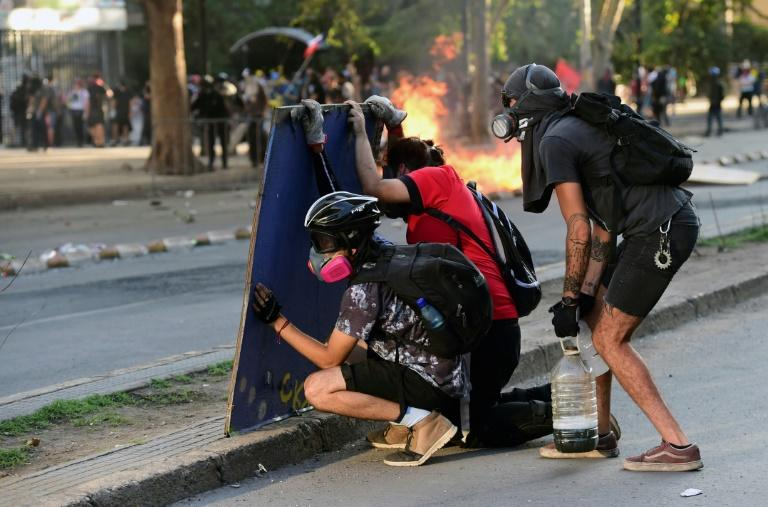 Demonstrators clash with riot police during a protest against the government in Santiago on Monday