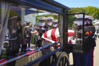 A Marine team places U.S. Marine Corps, Pfc. John Franklin Middleswart casket onto the horse-drawn funeral carriage where it will escorted to the ceremony for full military honors at Fort Rosecrans National Cemetery on Tuesday, June 8, 2021, in San Diego. Eighty years after he died in the attack on Pearl Harbor and just months after his remains were finally identified, the California Marine has been laid to rest with full military honors. (Nelvin C. Cepeda/The San Diego Union-Tribune via AP)