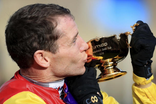 Jockey Richard Johnson kisses the trophy after winning the Cheltenham Gold Cup riding Native River, during the 2018 Cheltenham Festival at Cheltenham Racecourse, in Cheltenham, England, Friday March 16, 2018. (Mike Egerton/PA via AP)