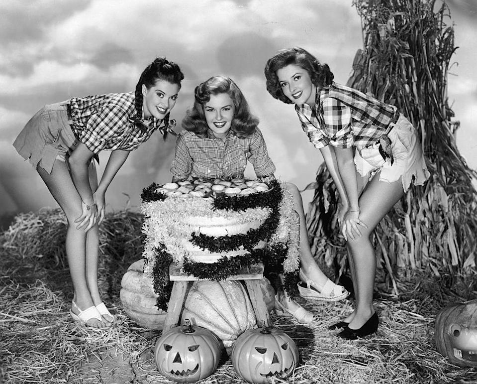 """<p>As fashion began to evolve and leg-baring became apropo, so did Halloween costumes. Here, three actresses dressed as """"girls on the farm"""" bob for apples. </p>"""