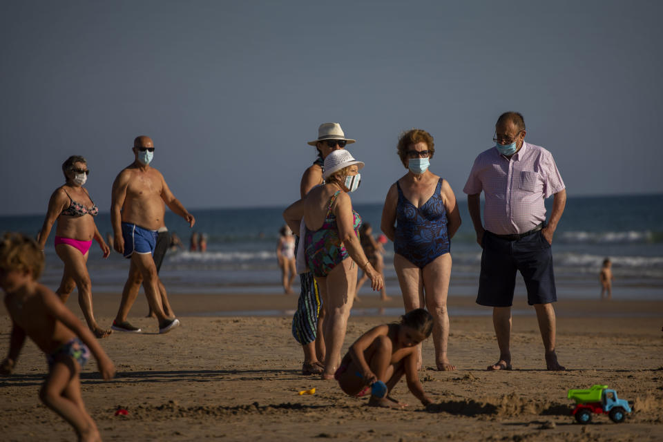 People wearing face masks stay at the beach in Barbate, Cadiz province, south of Spain, on Saturday, July 25, 2020. Ministers are set to remove Spain from the Government's list of safe countries to travel to after the European country saw a rise in Covid-19 cases. The decision means those coming back from Spain will have to self-isolate for two weeks upon their return to England. (AP Photo/Emilio Morenatti)