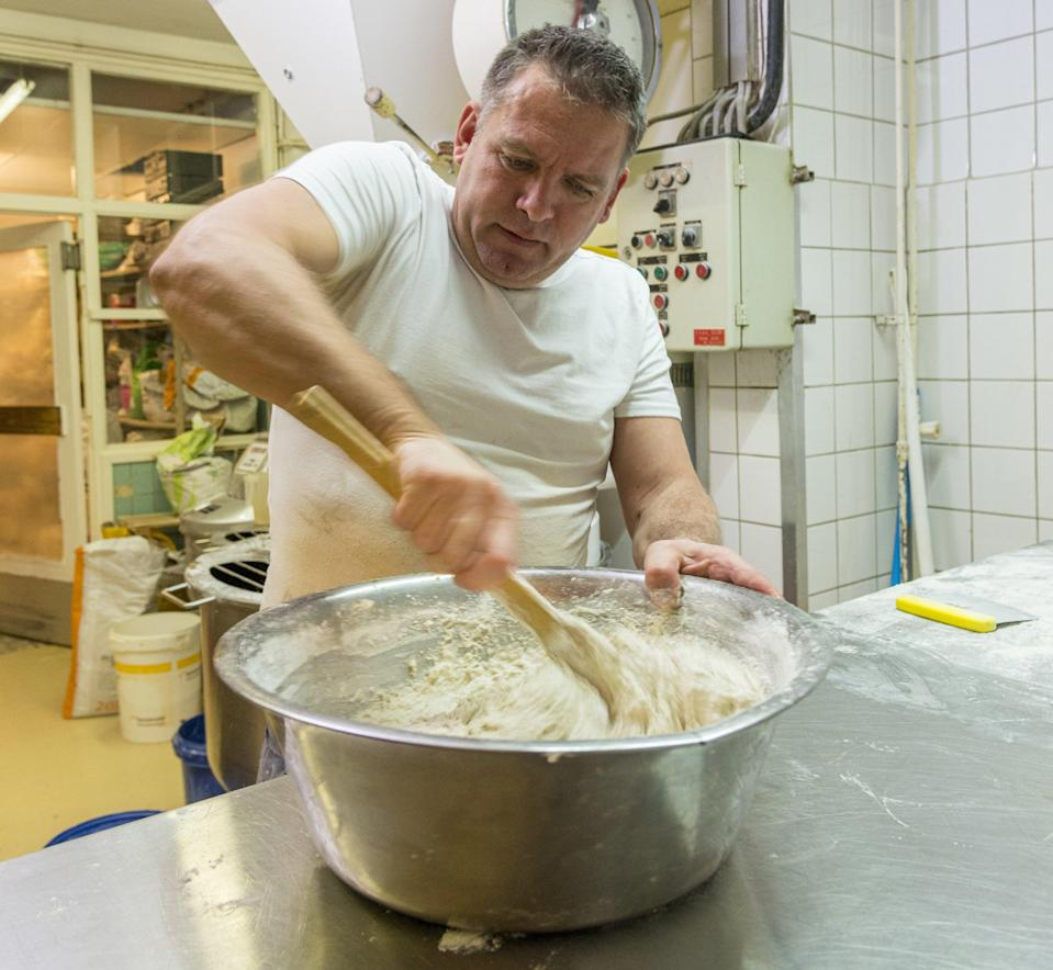 A man mixing dough in a large bowl.