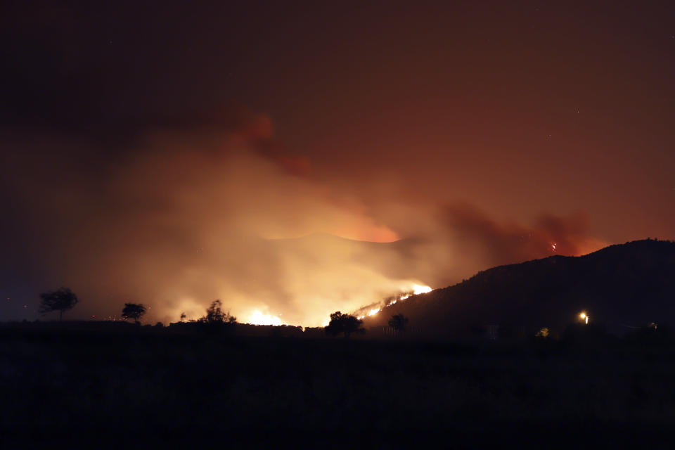 Flames illuminate the night sky and smoke after wildfires reached Kemerkoy Power Plant, a coal-fueled power plant, in Milas, in southwest Turkey, late Wednesday, Aug. 4, 2021. Nearby residential areas were being evacuated Wednesday evening as the flames reached the plant. (AP Photo/Cem Tekkesoglu)