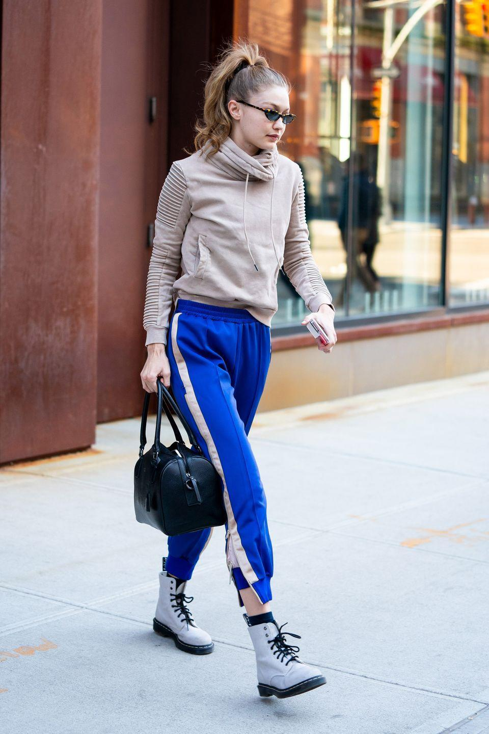 <p>In a khaki hoodie, blue sweat pants with white stripes down the side, white combat boots, tiny sunglasses, and a black handbag.</p>