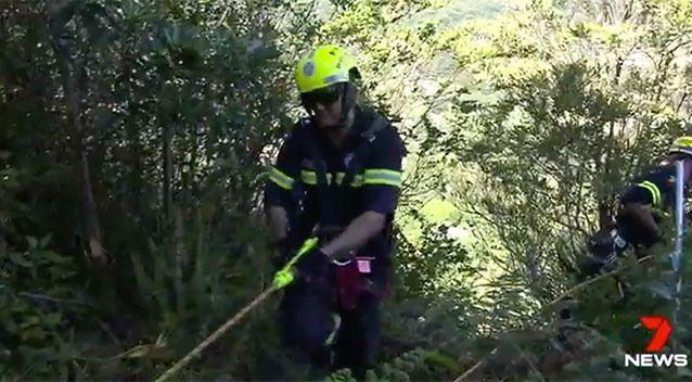 Volunteers abseil down the cliff at Currumbin. Source: 7 News