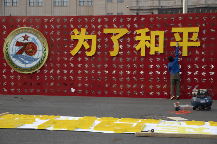 """In this Saturday, Sept. 28, 2019, photo, a worker puts up the words """"For Peace"""" for an exhibition on International Military Cooperation by the Chinese military to coincide with the 70th anniversary of the Founding of the People's Republic of China in Beijing. A parade on Tuesday, Oct. 1, 2019 by China's secretive military will offer a rare look at its rapidly developing arsenal, including possibly a nuclear-armed missile that could reach the United States in 30 minutes, as Beijing gets closer to matching Washington and other powers in weapons technology. (AP Photo/Ng Han Guan)"""