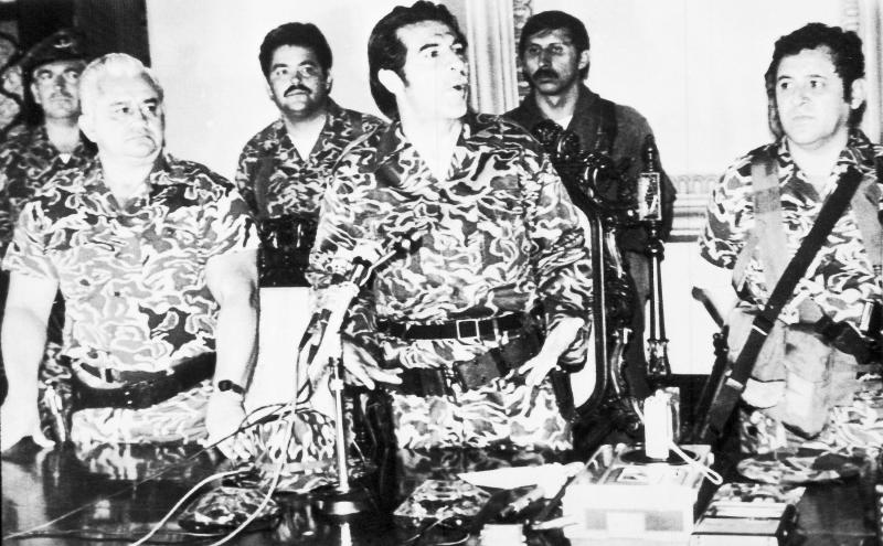 FILE - In this March 23, 1982 photo, General Efrain Rios Montt, center, speaks at a press conference in Guatemala City, where he announced the formation of a junta in the aftermath of the overthrow of General Fernando Romeo Lucas Garcia's right wing government. At left is General Horacio Maldonado Shad and right is Colonel Luis Frandisco Gordillo. Rios Montt rose to power in this March 23, 1982 coup d'etat, holding absolute power for just over a year before he himself was overthrown. Prosecutors say that while he was head of state he was aware of, and thus responsible for, the slaughter by his subordinates of at least 1,771 Ixil Mayan people who lived in the towns of San Juan Cotzal, San Gaspar Chajul and Santa Maria Nebaj, in the Quiche department in Guatemala's western highlands. (AP Photo, File)