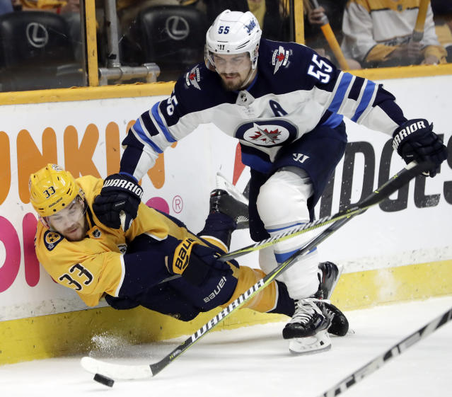Nashville Predators left wing Viktor Arvidsson (33), of Sweden, tries to pass the puck as he is checked by Winnipeg Jets center Mark Scheifele (55) during the second period in Game 2 of an NHL hockey second-round playoff series Sunday, April 29, 2018, in Nashville, Tenn. (AP Photo/Mark Humphrey)
