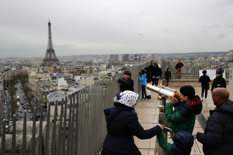FILE - In this March 21, 2017, file photo, tourists watch Paris from the top of the Arc de Triomphe in Paris, France. The Eiffel Tower is seen background. The American Society of Travel Agents is starting to refer to agents as