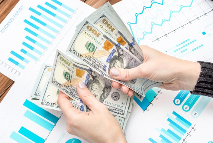 Businesswoman counting money over business charts on a desk
