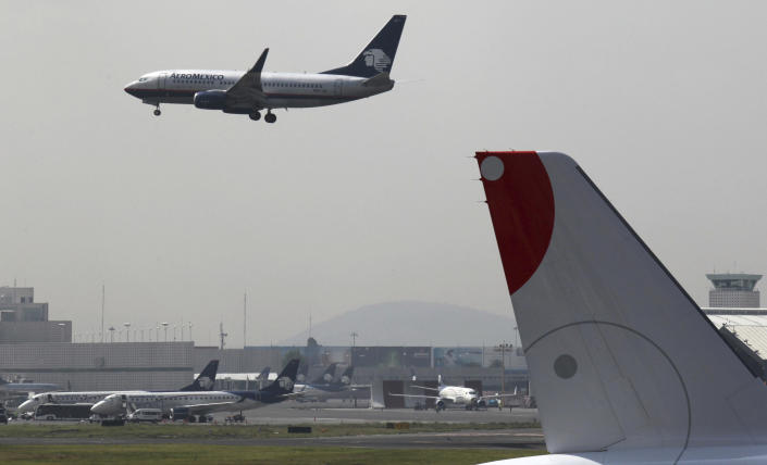FILE - In this July 8, 2015 file photo, a plane prepares to land at the Benito Juarez International Airport in Mexico City. A $15.7-billion project for a new airport, which is about one-third completed and located next to Lake Nabor Carrillo, is threatening a decades-old effort to restore the lakes that originally covered the valley in which the capital is located. (AP Photo/Marco Ugarte, File)