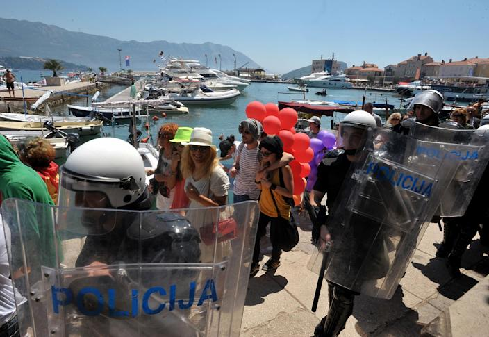 """Montenegro gay activists march during the first ever pride event in the Montenegrin seaside resort of Budva, Wednesday, July 24, 2013. Dozens of extremists shouting """"Kill the gays"""" have attacked gay activists as they were gathering for the event in staunchly conservative Montenegro. The assailants threw rocks, bottles and various other objects at some 20 gay activists and supporters and at special police securing the event in the coastal town of Budva on Wednesday. Police intervened to push the attackers away and the event continued as planned. (AP Photo/Risto Bozovic)"""