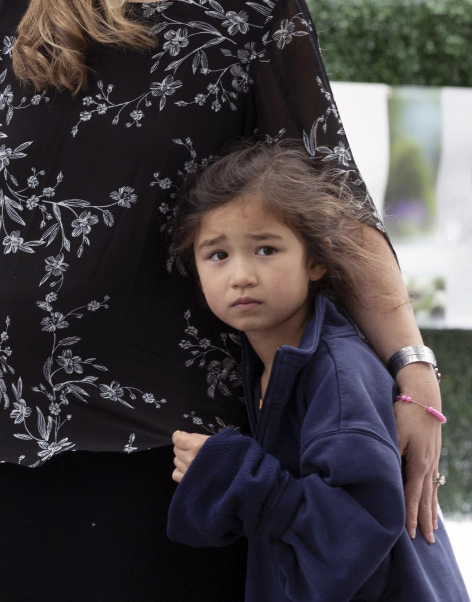 Brigit Hammond-Lau, 5, hugs her mother Ingrid Hammond during a ceremony at the Massachusetts Fallen Heroes Memorial, Saturday, Aug. 28, 2021, in Boston. The ceremony was held to honor the U.S. service members killed in a suicide bombing at the airport in Kabul, Afghanistan, including Marine Sgt. Johanny Rosario Pichardo from Lawrence, Mass. (AP Photo/Michael Dwyer)