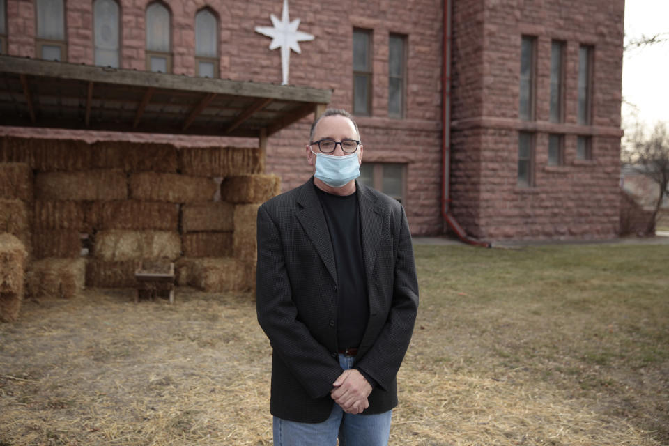 Rev. Tim Thies poses in front of the empty Nativity stable at Canton Lutheran Church in Canton, South Dakota on Dec. 8, 2020. The church decided to cancel a live Nativity performance this year after fears a large gathering could lead to more coronavirus deaths in the community. (AP Photo/Stephen Groves)