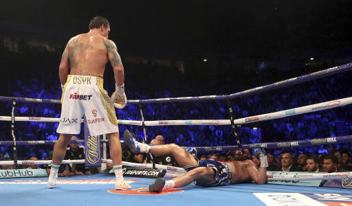 Tony Bellew, right is knocked down in the eighth round by Oleksandr Usyk during their cruiserweight boxing bout Saturday, Nov. 10, 2018, in Manchester, England. Usyk successfully defended his four belts and likely sent Bellew into retirement by knocking out the British fighter in the eighth round. (Nick Potts/PA via AP)
