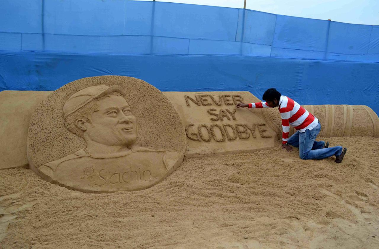 "Indian sand artist Sudarsan pattnaik gives the final touches to his sand sculpture of Indian cricketer Sachin Tedulkar with the message ""Never say Goodbye"" at Cuttack, some 25 kilometers from Bhubaneswar on November 16, 2013.  Indian cricket legend Sachin Tendulkar wept as he left the pitch for the final time after his 200th Test match, ending a dazzling career spanning nearly a quarter of a century.   AFP PHOTO/ASIT KUMAR        (Photo credit should read ASIT KUMAR/AFP/Getty Images)"