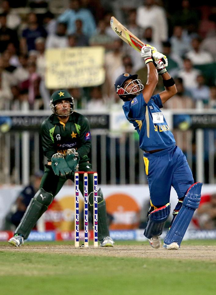 SHARJAH, UNITED ARAB EMIRATES - DECEMBER 18: Dinesh Chandimal of Sri Lanka bats as Umar Akmal of Pakistan looks on during the first One-Day International (ODI ) match between Sri Lanka and Pakistan at the Sharjah Cricket Stadium on December 18, 2013 in Sharjah, United Arab Emirates.  (Photo by Francois Nel/Getty Images)