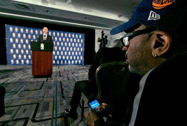 Filmmaker Spike Lee, right, watches as NBA Commissioner Adam Silver addresses a news conference in New York, Tuesday, April 29, 2014. Silver announced that Los Angeles Clippers owner Donald Sterling has been banned for life by the league in response to racist comments the league says he made in a recorded conversation. (AP Photo/Richard Drew)