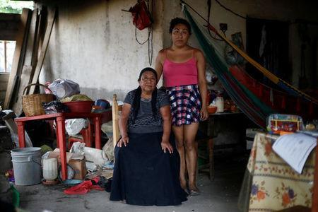Ximena, 26, an indigenous Zapotec transgender woman also know as Muxe, pose for a photo next her mother inside her house destroyed after an earthquake that struck on the southern coast of Mexico late on Thursday, in Juchitan, Mexico, September 10, 2017. REUTERS/Edgard Garrido
