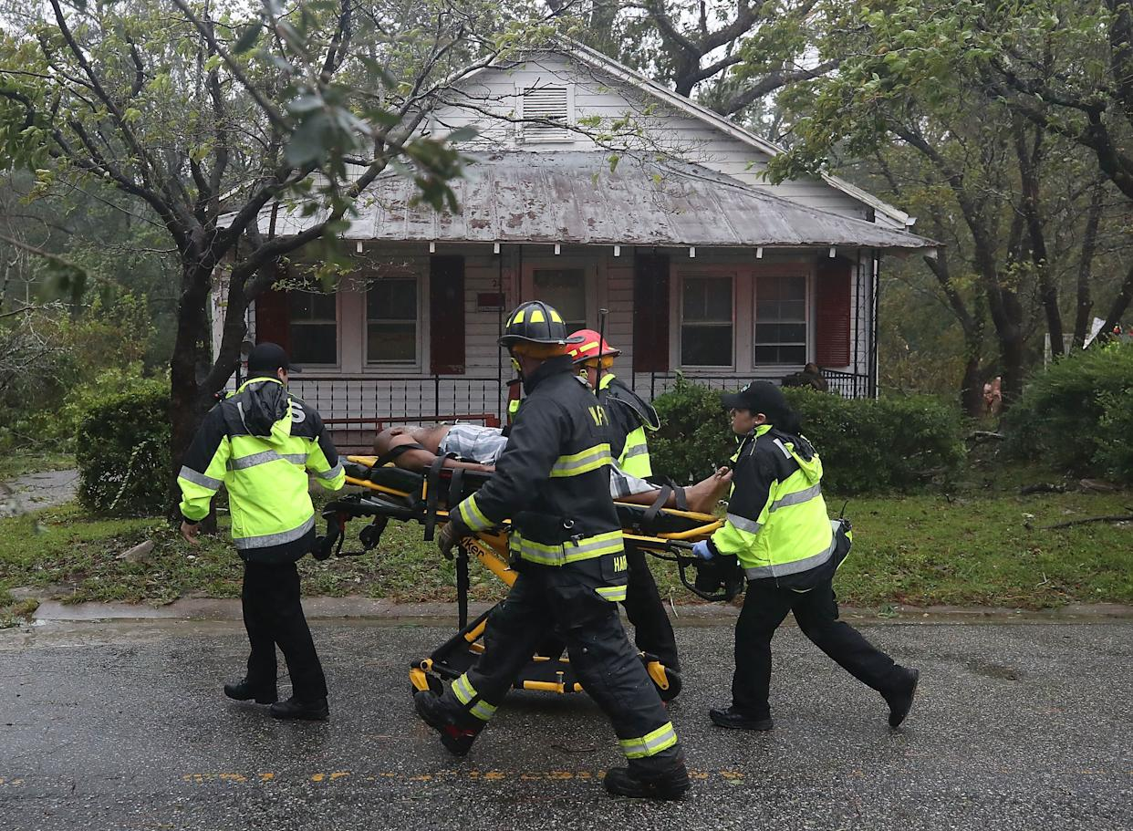 Rescue personnel remove a man from a home that a large tree fell on that had three people trapped after Hurricane Florence hit the area on Friday.