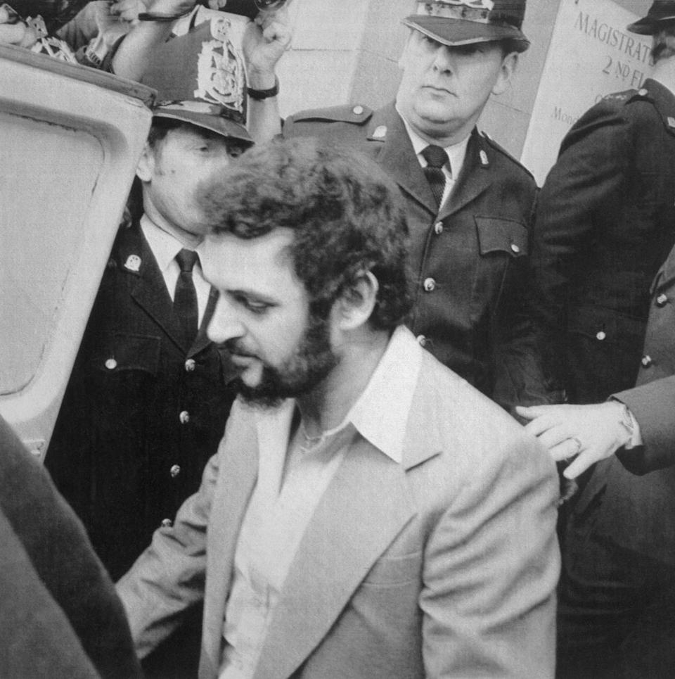 Yorkshire Ripper, Peter Sutcliffe, is shown leaving court under heavy police guard. (Getty)